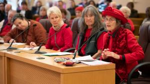 Residents wear red n opposition of fossil fuel development, ask County to take action.