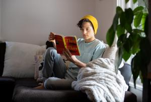 Curling up with a good book is one way to redirect anxious thoughts during home isolation.