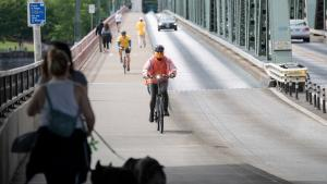 A masked bicyclist rides across Multnomah County's Hawthorne Bridge during the COVID-19 pandemic in 2020.