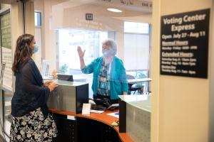 Elections staff wearing a face mask and behind plexiglass waves to voter wearing a face mask that she is helping at the Voting Center Express in Gresham