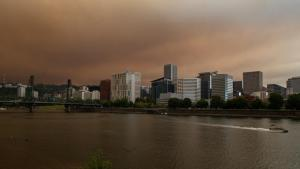 Smoke fills the sky above the Willamette River with downtown Portland in the background