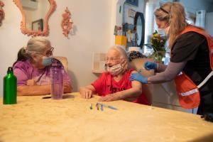 Medical Reserve Corps volunteer Dr. Aviva Zigman administers the COVID-19 vaccine to Carol Hansen, center, and Vivian Wescott, left.