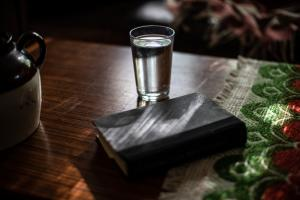 Water glass in a room with shades drawn to avoid heat.