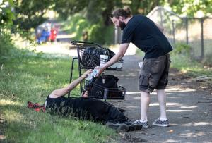 Michael Phelps, outreach worker/case manager, hands out water along with other care items under the record-breaking heat in SE Portland. Cascadia Behavioral Healthcare's Street Outreach Team also offers mental health and housing education.