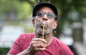 """""""I am planting positive seeds,"""" said Jerry Hunter, blowing a dandelion seed head at the Hands of Wonder garden."""