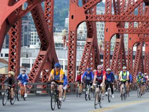Large number of people on bikes filling the two eastbound lanes of the Broadway Bridge, with distinctive red girders around them and the Pearl District in the background.