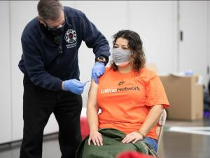 Latino Network employee receiving vaccine