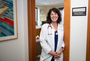 Commissioner Sharon Meieran standing in the oak doorway of her office wearing her white doctor's coat and stethoscope.