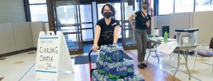 Two volunteers in masks inside a County cooling center; one volunteer pushes a cart of water bottles
