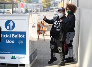 Voters return ballots to an Official Ballot Drop Site outside the Multnomah County Duniway-Lovejoy Elections Building