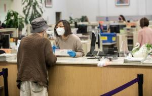 An elections worker wearing gloves and a face mask helps a voter from behind plexiglass at the Multnomah County Duniway-Lovejoy Elections Building.