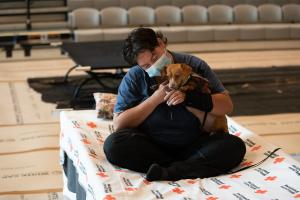 Guest hugs dog at Kellogg Middle School cooling center.