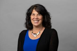 A portrait photo of Commissioner Meieran. She is wearing a royal blue shirt, black cardigan, multicolored necklace, and is smiling in front of a light grey background.