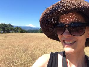 Picture of woman with hat and sunglasses in the foreground and Mt. Hood in the background