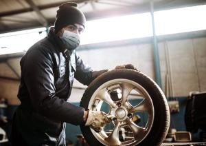 Person at work on a car wheel wearing a mask
