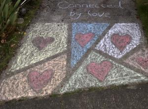 """Sidewalk chalk of hearts with the title, """"Connected by Love""""."""
