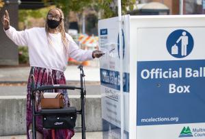 Voter holding ballot next to Multnomah County ballot drop box