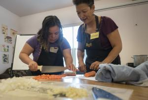 Chrystal Figueroa gets some help from chef Allison Lew during the irstin a series of cooking classes offered through the Oregon Food Bank