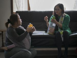 IRCO's Sivheng Ung and her client Lal Nun Puii finish a Healthy Families session by trying out a new toy intended for 2-year-old Bethany.