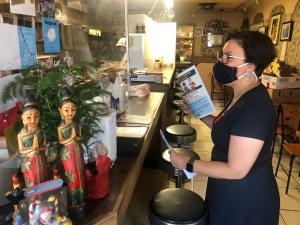 Commissioner Vega Pederson passes out flyers at a local business