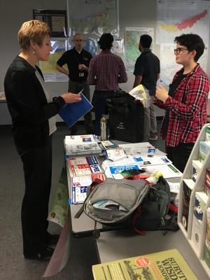 An intern staffs an informational table at an event.