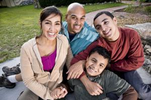 Latino family smiling outside.