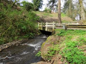 A side view of a small wooden bridge with a white wooden fence over a creek.