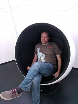 Man in white chair shaped like an egg with one piece cut out. He has stubble on his face, wearing a brown t-shirt blue jeans and canvas shoes.