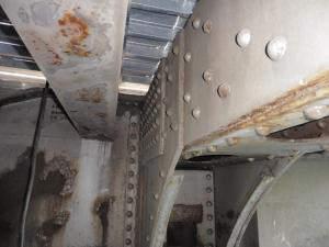 A view of structural steel members on the underside of a bridge. Their paint is peeling in spots, and rust and corrosion can be seen.