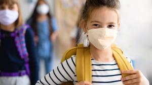 School girl looking at camera wearing mask