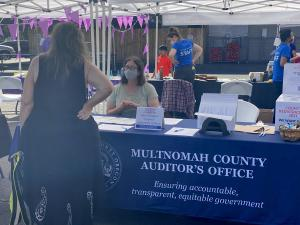 Auditor McGuirk sits at a table at the 9/25/21 Saturday Celebrations event and talks with a community member.