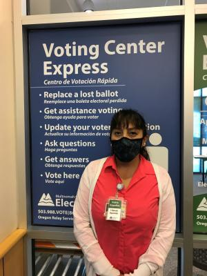 Susy Kristin, elections worker poses in front of the Gresham Voting Center Express bilingual sign in Gresham. She wears a black face covering, a pink shirt, and white sweater. She has a badge pinned to her shirt that says Habla Español.