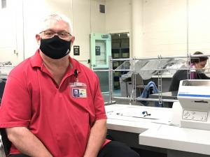 Tom Urbanowicz, election worker sits at a ballot extration table. He wears a black face covering and red colored shirt. There is a woman working at a machine behind him and an open green door in the background.