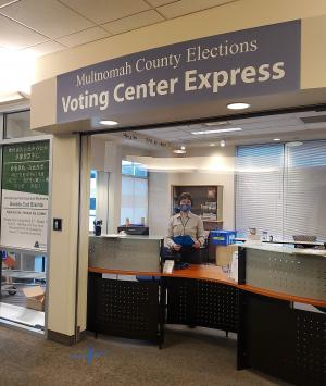 Election staff wearing a mask and holding a clipboard stands in front of the Voting Center Express in Gresham.