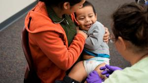 Mom holding toddler who is getting an immunization in his leg.