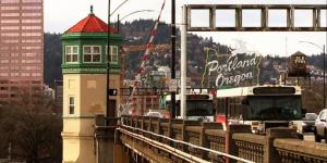 An operator tower of the Burnside Bridge with the Portland Oregon sign and West Hills in the background