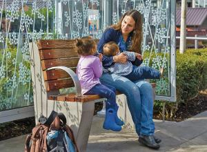 nursing mom with two children at a transit station