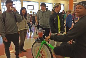 students gathered around a stationery bike being used to power a blender
