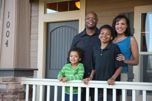African American family smiling in front of their home