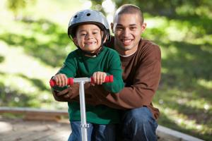 boy posing on scooter with dad