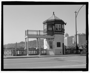 Black and white image of the bridge operator's house on the Burnside Bridge, with parts of downtown and Marquam Hill in background. House is two stories with a cupola on top and a long portico supported pillars emerging from the second floor.
