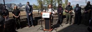 Chair Kafoury standing behind a lectern; seven other County and community leaders standing on either side of her; Portland downtown skyline in the background