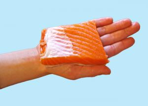 Child's hand holding a piece of raw fish