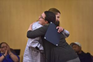 Justice Reinvestment program graduate hugs a service provider during a March graduation ceremony.