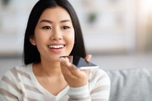 Happy woman using virtual voice assistant