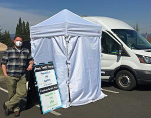 health worker standing next to a clinic van and privacy tent in a parking lot