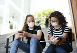 Picture of two masked students with backpacks sitting on stairs and looking at a book