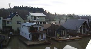 A moorage with several floating homes at wooden docks.