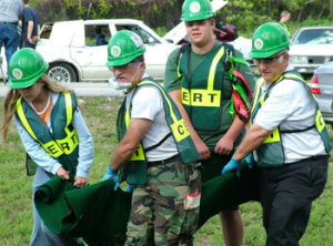 Volunteers wearing hard hats and vests practice carrying a fake victim