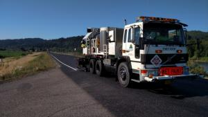 A striping truck with a Multnomah County logo and an orange 'Wet Paint' sign lays down a white stripe along the edge of a road on top of an embankment, with a river in the background.